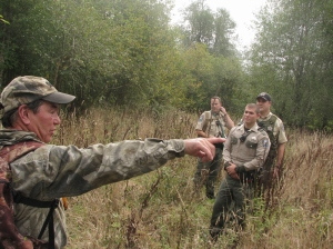 Bear attack victim Jerry Hause leads a team of state fish and game wardens through the backwoods he was hunting before an angry bear chased him up a tree and bit and scratched his leg. Photo by Brooks Johnson