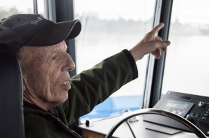 Dave Schmelzer talks about past river adventures while co-piloting the Oscar B up the Columbia River on Friday morning. Schmelzer, a retired tugboat pilot, took turns guiding the ferry with the son of the real Oscar B, Gary Bergseng. Photo by Brooks Johnson